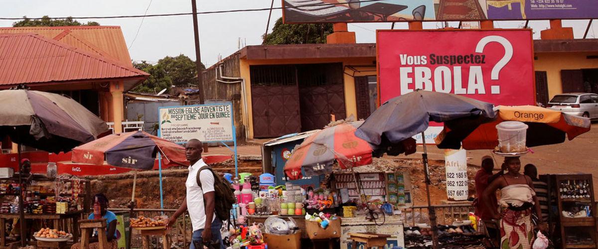 Scène de rue à Conakry avec affiche 'Vous suspectez Ebola?'